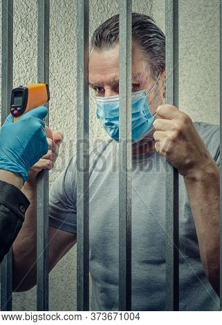 Measuring Temperature With An Infrared Thermometer To A Prisoner In A Jail Cell