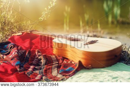 Guitar On A Blanket On The Ground In Nature.