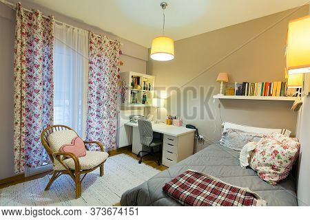 Cozy Interior Bedroom Of A Young Woman With White Laminate Desk, A Bamboo Chair, Single Bed, Books O