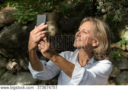 Senior Woman, 61 Years Old, Wearing A Shirt Is Taking A Selfie, Upper Body, Daylight, Nature Backgro