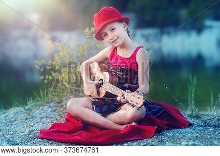 Little Girl Sitting On Blanket And Playing Ukulele, Outdoor Portrait.