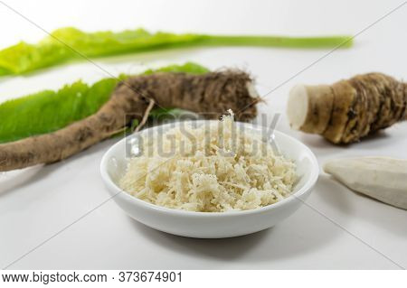Grated Horseradish In A Small Bowl, Fresh Roots And Leaves Blurry In The Light Gray Background, Sele