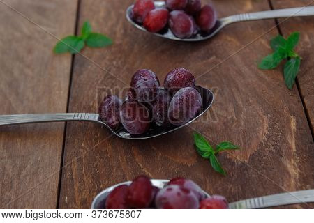 Red Berries Of Frozen Grapes And Dogwood In Tablespoons With Mint Leaves On A Brown Wooden Backgroun