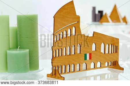 Served Table With Italy Topic Decorated By Green Candles And Wooden Coliseum