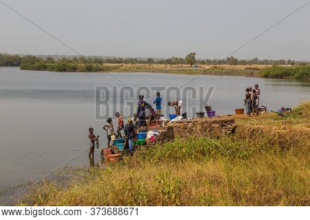 Bissau, Guinea-Bissau - January 5, 2020: group of African Kids playing in the river, in rural Guinea-Bissau