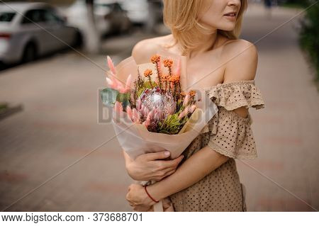 Young Woman In Beige Dress Neatly Holds In Her Hands Beautiful Exclusive Flower Bouquet