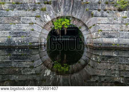 Detail of an old stone dam reflecting in water at Milngavie Waterworks, the water treatment facility located in Milngavie, Scotland.