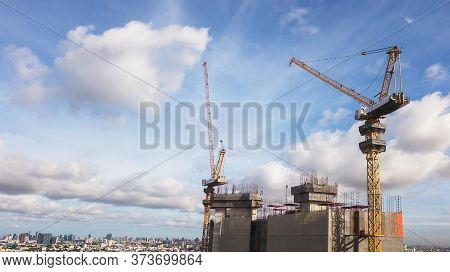Large Construction Site Including Several Cranes Working On A Building Complex, With Clear Blue Sky