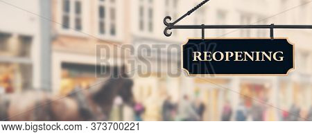 Reopening Economy Concept. Sign With Word Reopening Hanging Against Open Shop Windows Background. Re