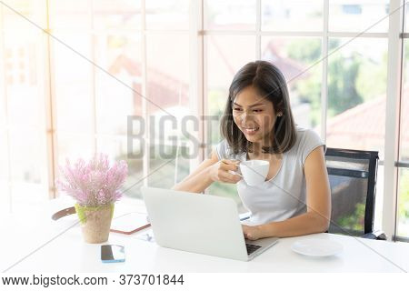 Portrait Of Smiling Happy Beautiful Asian Woman Using Technology Of Laptop Computer While Sitting, D