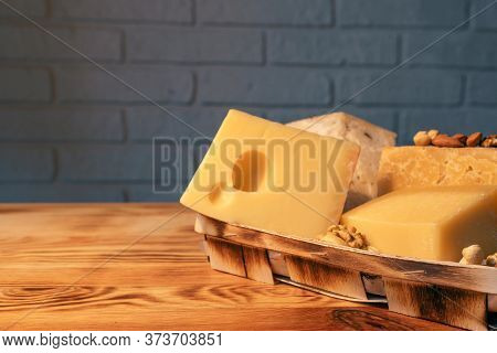 A Variety Of Aged Cheeses In A Substrate On A Wooden Table