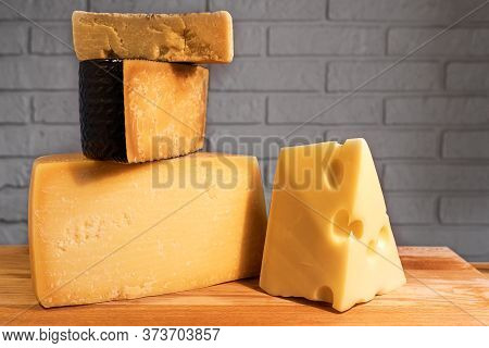 Pyramid Of Various Cheeses On A Wooden Board