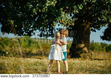 Happy Little Friends Hugging On Countryside. Child Embrace Each Others. Funny Kids, Cute Little Boy