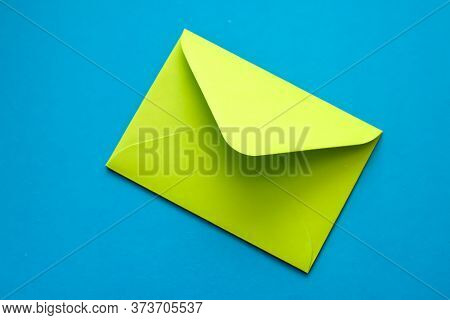 Green Envelope On A Blue Background. Postal Envelope. Love Letter. Colorful Photo Of The Postal Enve