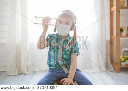 Little Cute Kid Boy In Quarantine At Home Dreams Of Traveling.