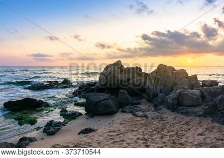 Idyllic Sunrise On The Ocean Shore. Waves Crashing Rocks On Sandy Beach. Beautiful Cloudscape Above