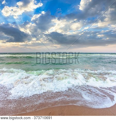 Golden Beach And Green Sea On A Cloudy Evening. Beautiful View Of Waves Rolling The Coast Beneath A