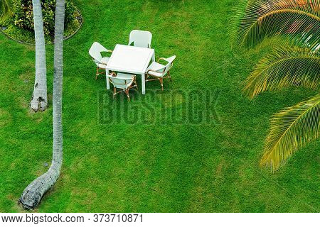 A Dining Setting On Vivid Green Grass Surrounded By Tropical Trees At A Relaxing Mainland Resort
