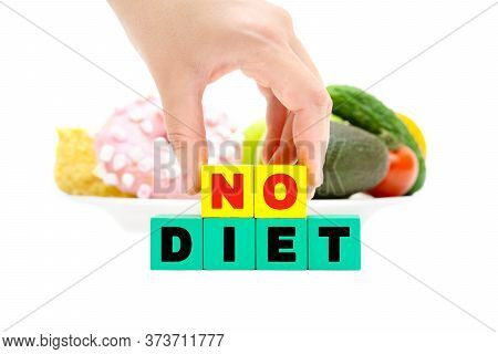 Female Hand Holding Wooden Text Blocks Spelling No Diet In Front Of A Plate With Vegetables And Donu