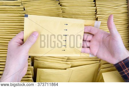 Male Hands Open A Yellow Bubble Envelope Against The Open Shipping Box Full Of Padded Mailers. Close