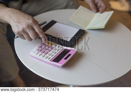 Hand Of Man Hitting Calculator While Looking At Bankbook.