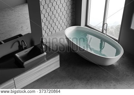 Top View Of Stylish Bathroom With Gray Honeycomb Tile Walls, Concrete Floor, Comfortable Bathtub And