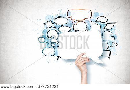 Hand Of Woman Holding Blank Speech Bubble Near Concrete Wall With Speech Bubbles And Thought Clouds