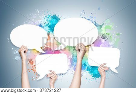 Woman Hands Holding Blank Speech Bubbles Over Grey Wall Background With Colorful Paint Splashes. Con