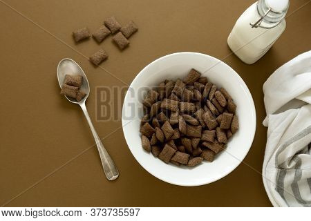 Fast Carbohydrates, Junk Food. Chocolate Cereal Rings In Bowl Brown Background.