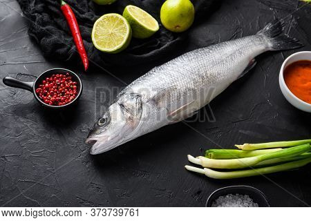 Seabass With Spices And Herbs Ingredients  On Black Background Side View Space For Price.