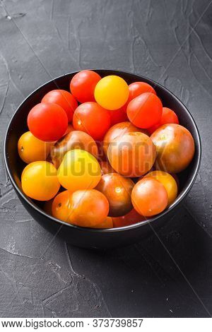 Cherry Tomatoes In Bowl On Black Background Side View.