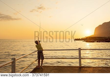 Teenager Boy Catching The Fish From The Pier At Sunset, Black Sea, Crimea