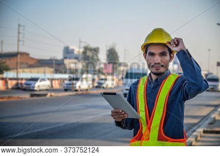 Road Construction Engineers Are Using Tablets To Inspect Construction Projects On A Traffic Backgrou