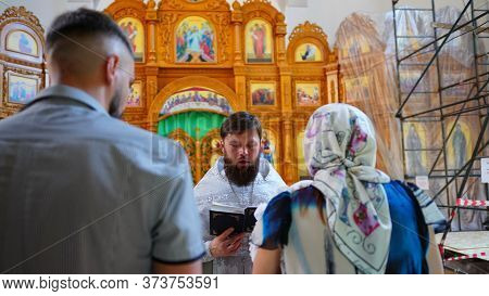 The Sacrament Of Baptism. Priest Holding Ceremony Of Orthodoxal Christening The Baby In Chirch. Prie