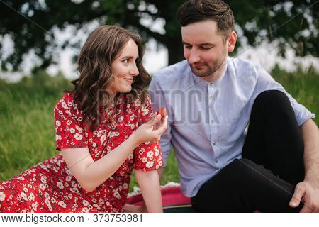 Attactive Young Woman With Handsome Man Sits Outdoors On Red Blanket. Woman Give To Man Strawberry.