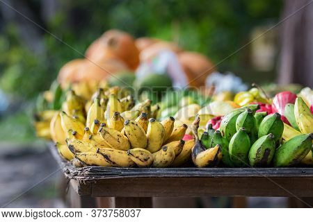 Bananas And Green Platanos Oon A Wooden Table Outdoors On The Main Street Of Praslin, Seychelles.