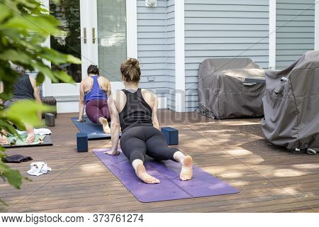 Women Doing A Virtual Yoga Class At Home Outside During Covid-19 Coronavirus Pandemic.  Social Dista