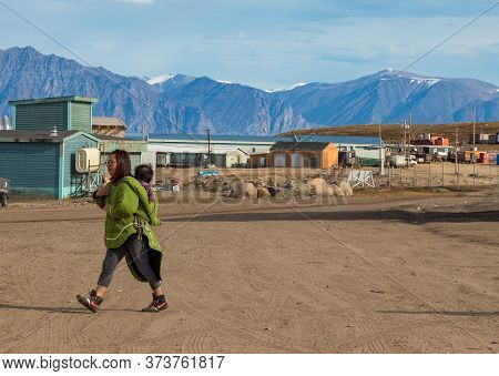 Pond Inlet, Baffin Island, Canada - August 23, 2019: Eskimo - Inuit Woman Carrying Her Baby On Her B