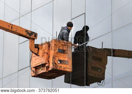 Petropavlovsk, Russia - September 16, 2019: Male Worker Cleaning Windows Standing On A Crane, Outdoo