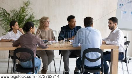 Interested Diverse Employees Listening To Mentor At Meeting In Boardroom