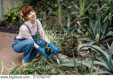 Portrait Of Young Happy Caucasian Red Haired Woman In Garden Working With Shovel And Smiling To Came