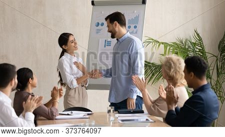 Smiling Executive Shaking Successful Arabic Businesswoman Hand At Briefing