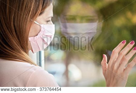 Young Woman In Pink Virus Mask Looking Sad From The Window Behind Glass Pane, Touching It With Hand.