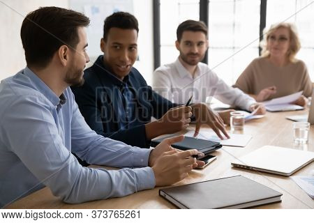 Diverse Colleagues Discussing Project At Corporate Meeting In Boardroom