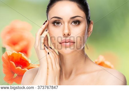 Beautiful Woman Face Portrait Over Flowered Blurred Background. Beauty Skin Care Concept
