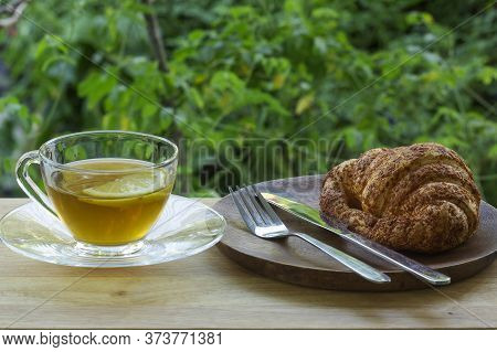 Hot Tea With Croissant Bread On  Wooden Bar Served In The Garden