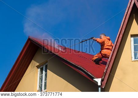 Reykjavik, Iceland - August 08, 2019: A Male Worker Cleaning A Roof With High Pressure Water In Icel