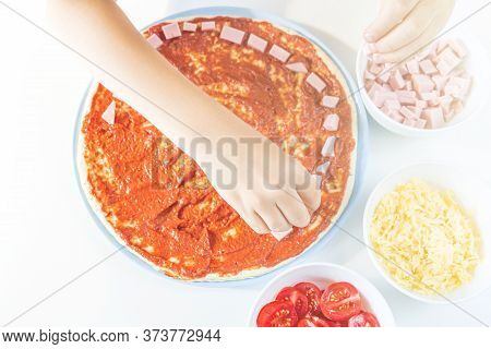 Process Of Cooking Homemade Pizza By Child. Step 3 Kid's Hands Spreads Ham Slices On A Dough. Step B