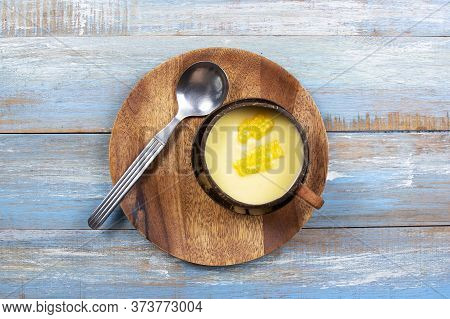 Cream Of Corn Soup In Wooden Bowl With Spoon