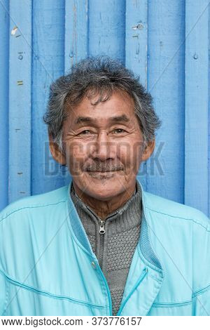 Nuuk, Greenland - August 16, 2019: Portrait Of An Inuit Local Mature Man Looking Camera Over A Strip